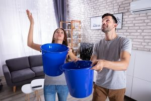 Young couple collecting water in the house