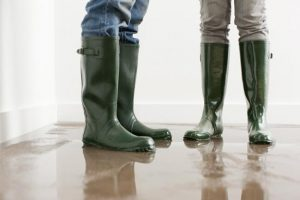 sewage and water damage restoration in Levittown, PA by ServiceMaster TEAM - 2 people with rubber boots standing on a flooded floor
