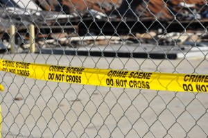 A bright yellow warning tape that reads Crime Scene Do Not Cross on a chain link fence