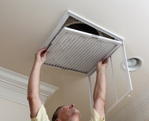 Senior male reaching up to open filter holder for air conditioning filter in ceiling