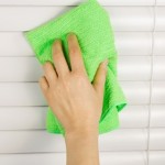 Vertical photo of female hand cleaning window blinds with microfiber cloth