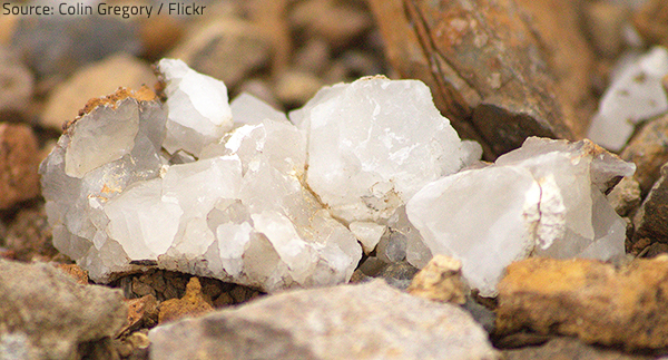 Natural quartz granules are combined with a binder and a colorant to create durable, non-porous quartz surfaces.