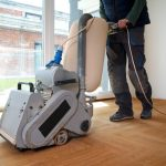 Sanding parquet with the grinding machine. Polishing, repair in apartment