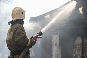 Fireman spraying water in a smouldering burnt out house