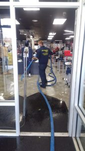ServiceMaster Technician Extracting Water Out of Store
