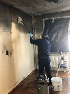 ServiceMaster Technician Cleaning Smoke Damage from the Walls