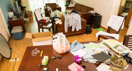 Hoarder Cleaning in Stoneham, MA is needed for this house. Everything from clothes to office supplies are scattered throughout this room.